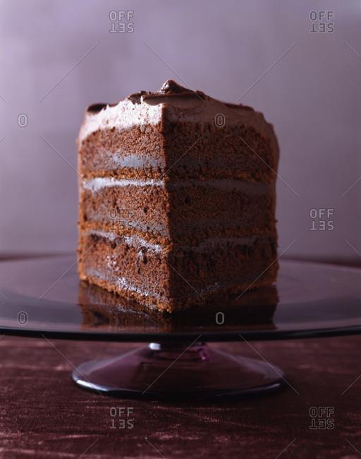 Piece of chocolate cake displayed on glass cake stand