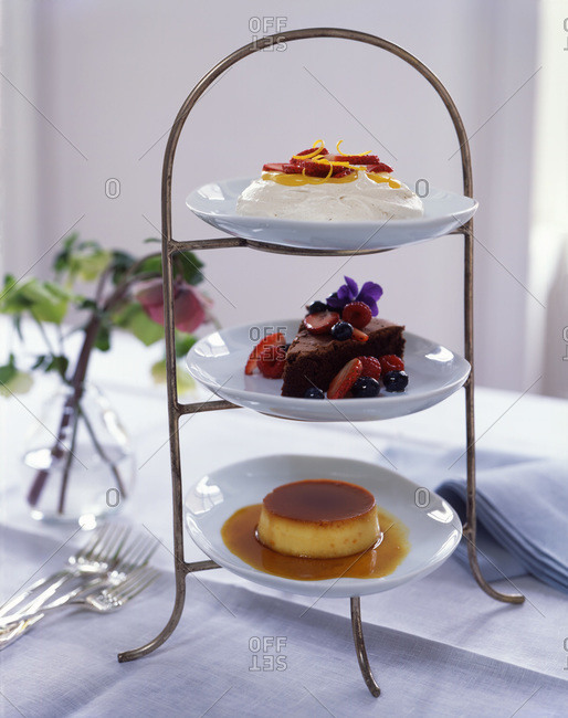 Three types of desserts served on 3 tier plate rack on the table