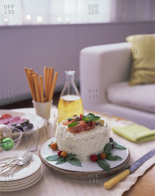 Savory layered cake with ham and cherry tomato topping  served at home
