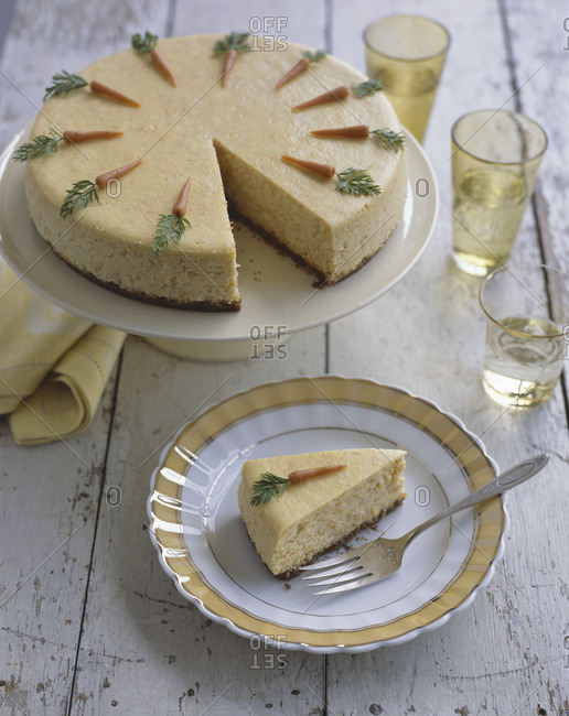 Round carrot cake served on cake stand in rustic interior