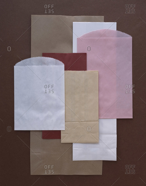 Paper packages of different sizes and colors arranged on brown background