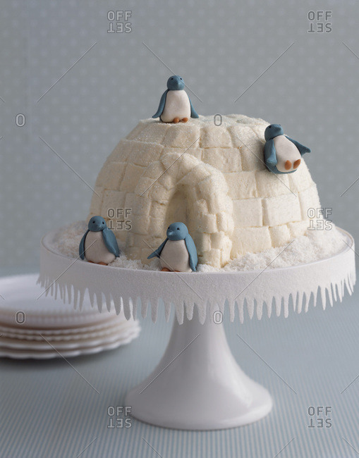 Festive coconut cake decorated with marzipan penguins and presented on cake stand