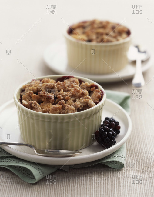 Golden blackberry crumble served in ramekins on the table