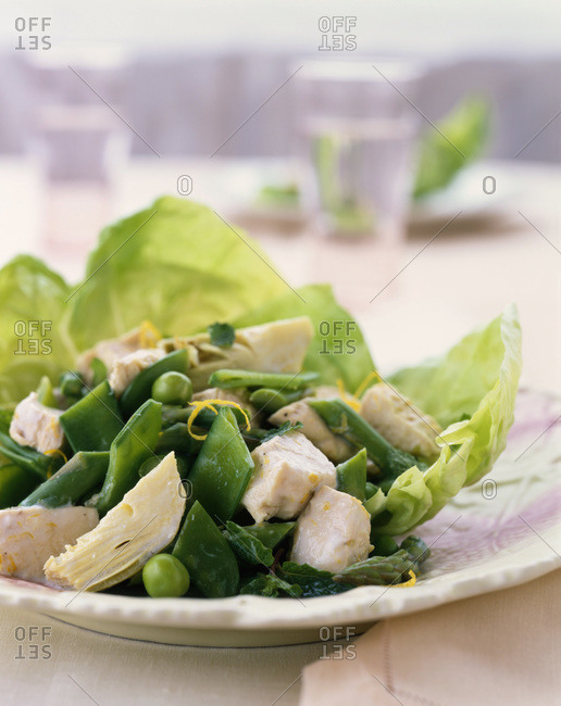 Green fresh salad with fish served outdoors