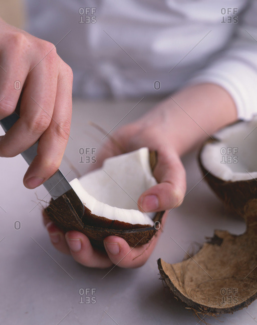Close up of hands skinning coconut