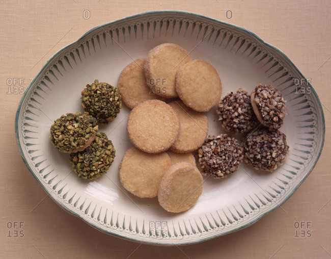 Collection of butter cookies with sugar and nut garnishing served on a dish