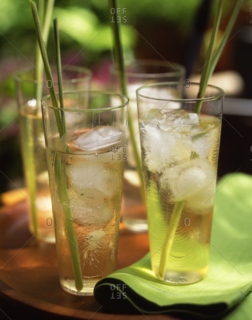 Icy lemonade served in tall glasses with grass garnish outdoors