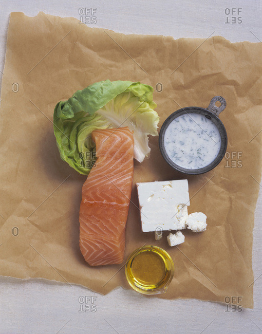 Composition with salmon, cheese and sauce displayed on textured paper