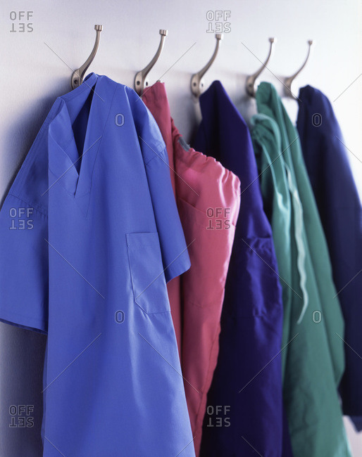 Colorful medical scrubs arranged on hangers in cloakroom