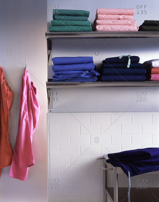 Colorful medical scrubs arranged on shelves in storage
