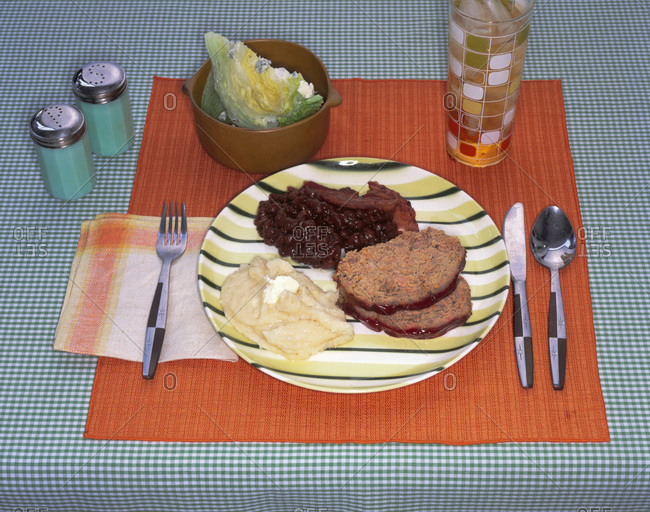 Party dinner: sliced meat roulade served with bean stew, smashed potatoes and salad