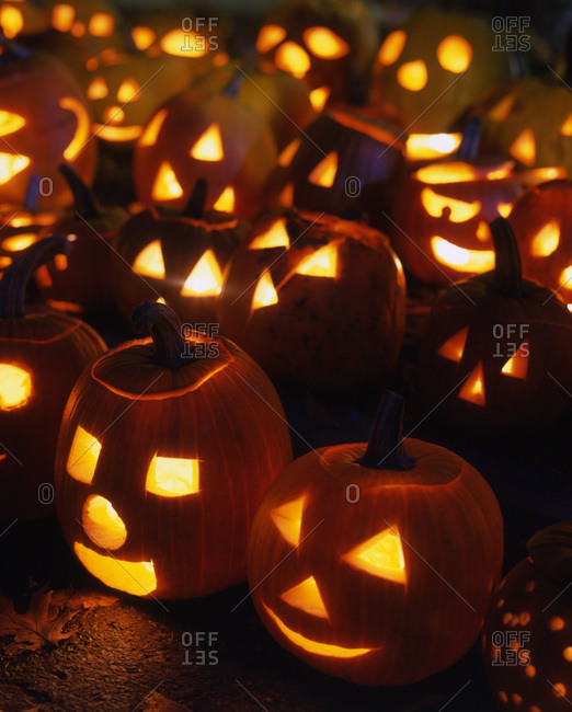 Party of carved Halloween pumpkins illuminated with candles