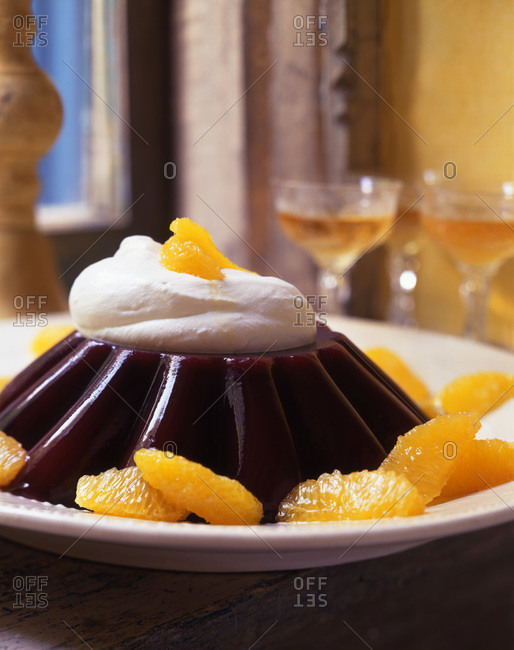 Tasteful fruit jelly served with cream topping and orange sections