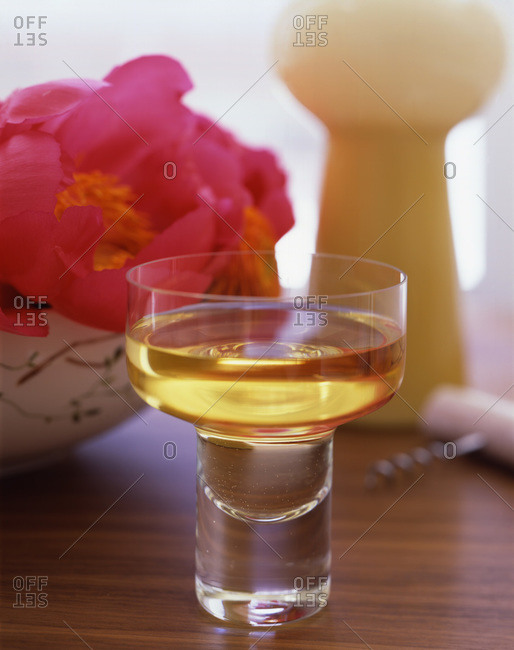 Composition with glass of white wine and pink flowers on the table