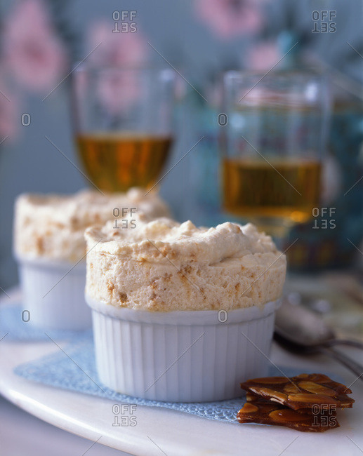 Fluffy almond souffle served in ramekins with brittle and dessert wine