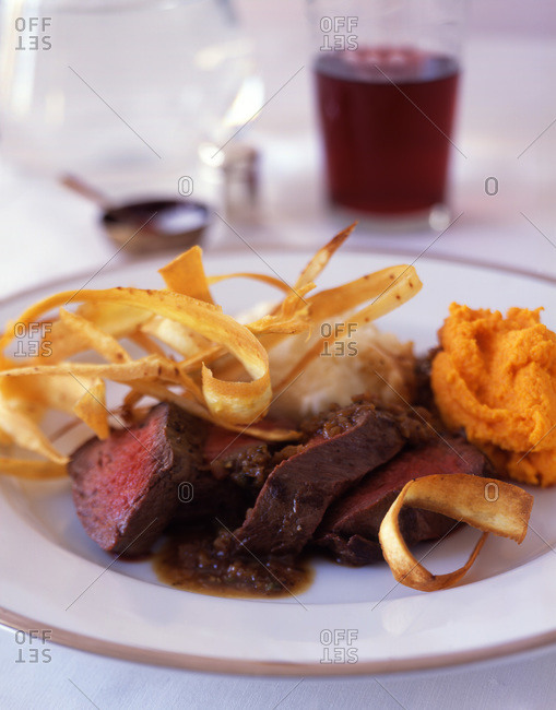 Beef steaks served with carrot chips and puree