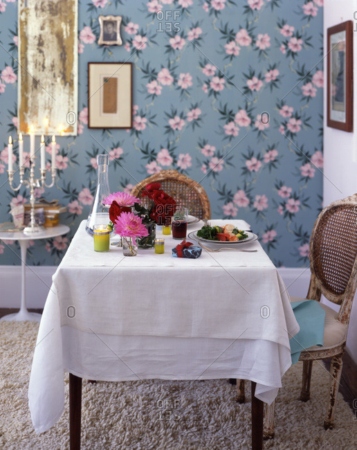 An ornate table setting in a room with flower pattern wall paper, shag carpet and a candelabra