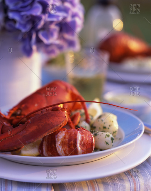 Lobster served with cooked potato in outdoor restaurant