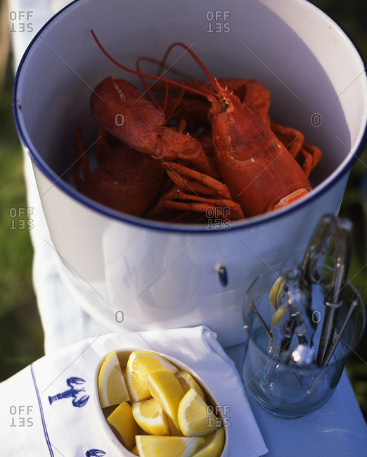 Lobster served in saucepan with lemon in outdoor restaurant