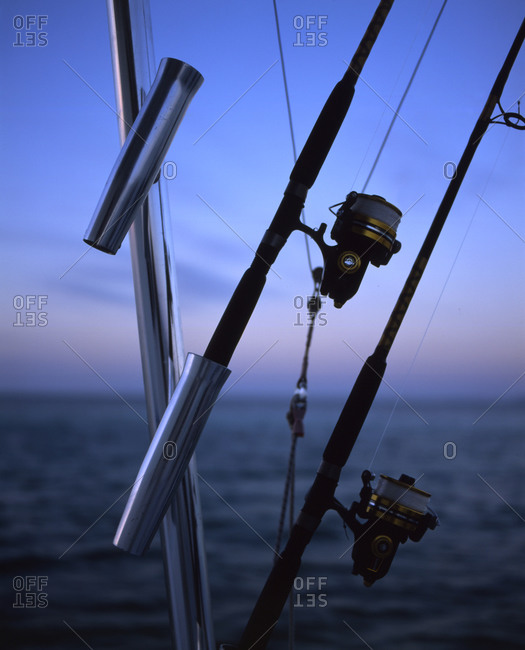 Close up of fishing rods in dusk on seashore