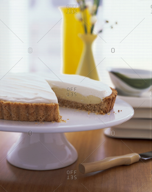 A key lime pie on a cake stand in a kitchen