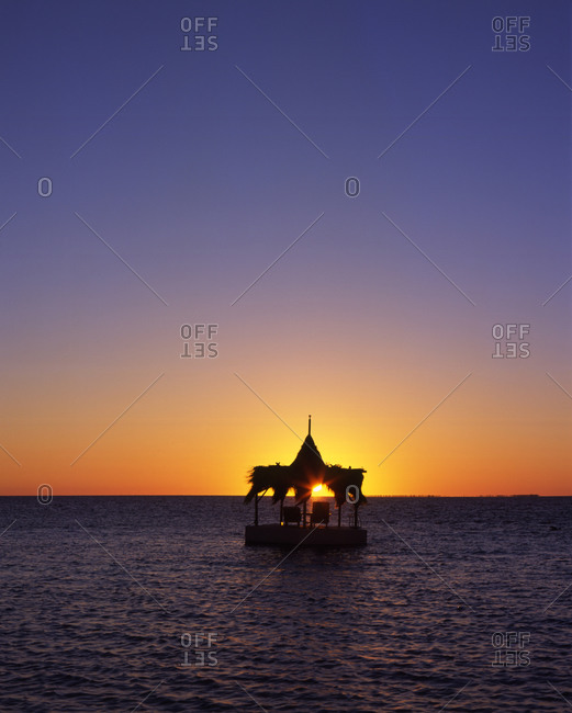 Panorama with exotic gazebo standing in water in dusk