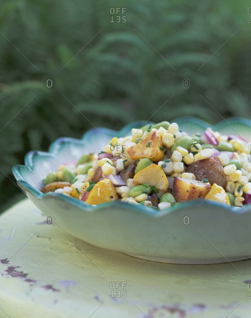 Corn and potato salad with chives seasoning served outdoors