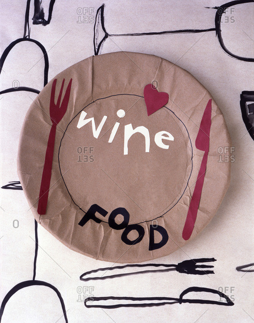 An artistic table setting featuring a plate with the words food and wine