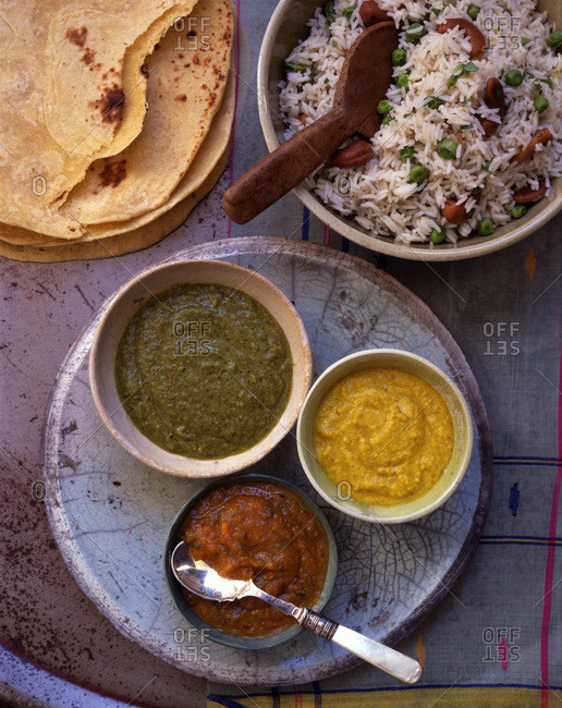 Composition with typical Indian dishes: rice with vegetables, chapati and variety of chutneys