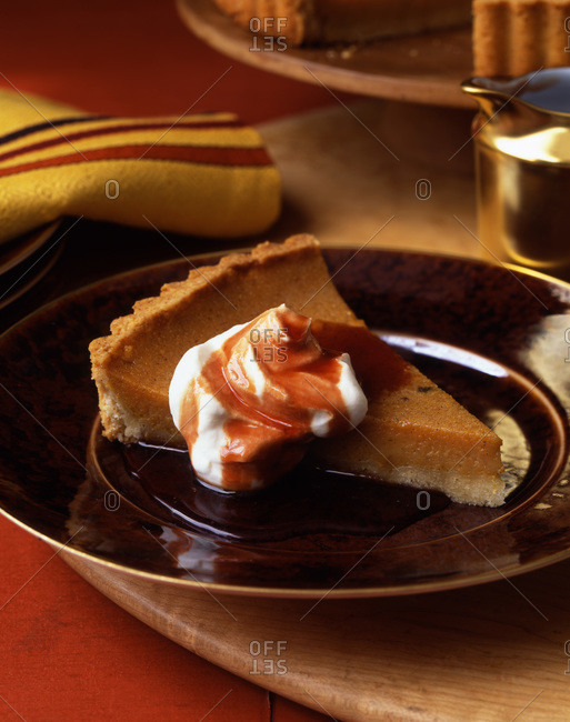 Piece of pumpkin tart served with whipped cream and sauce