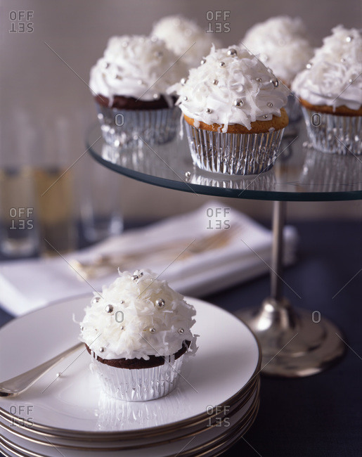 Chocolate cupcakes garnished with whipped cream, grated coconut and sprinkles