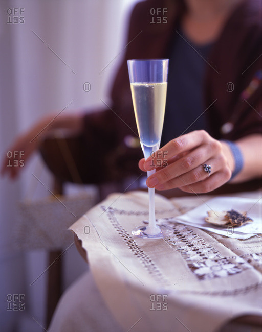 Woman's hand holding champagne flute