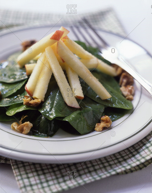 Spinach salad with apple and walnut served on a plate