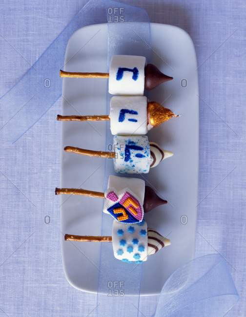Traditional Jewish dreidels made of marshmallows and pretzels and chocolate, decorated on the plate
