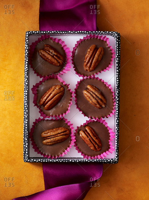 Tiny pecan pie truffles arranged in gift box with bright ribbon