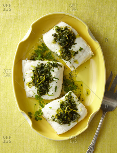 Top view of seasoned fish fillet served on yellow plate