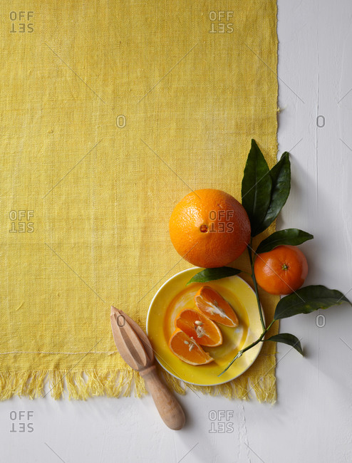 Composition with citrus fruits arranged on yellow tablecloth