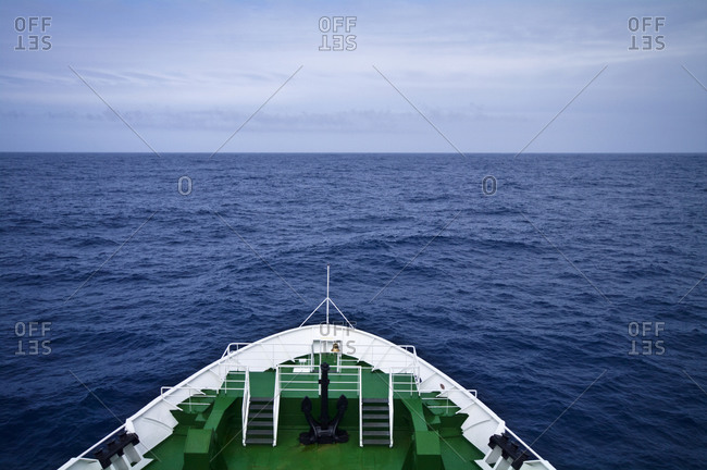 The bow of a ship heading towards a vast and distant ocean horizon
