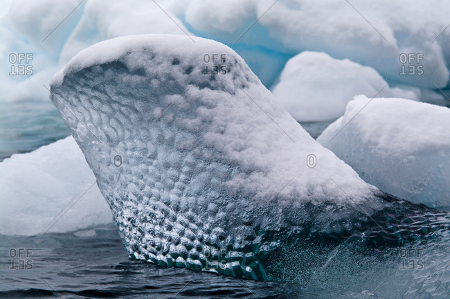 The translucent bubbled surface of a floating iceberg covered on snow