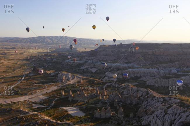 Hot air balloons fly at sunrise over Cappadocia