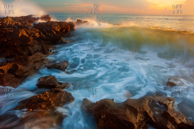 Incoming waves crashing on the limestone beach of Coral Cove State Park at sunrise in Florida