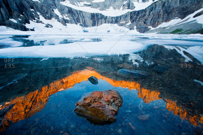 A shoreline rock and reflection of first light on the peaks Iceberg Lake, Glacier National Park, Montana