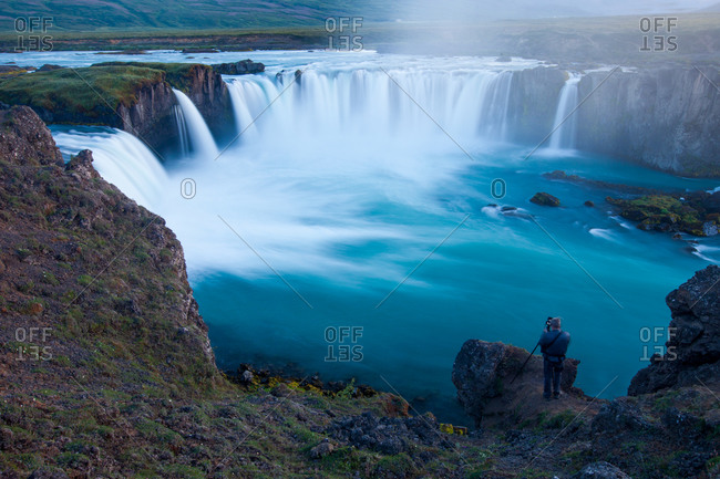 Photographer standing at the Godafoss waterfall, Iceland