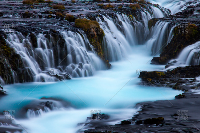 Glacial blue water spills over Bruarfoss waterfall in southwestern Iceland