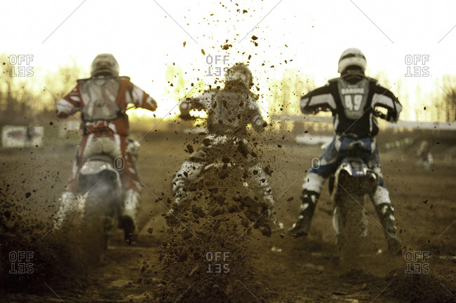 Back view of motorcycle racers kicking up mud during race