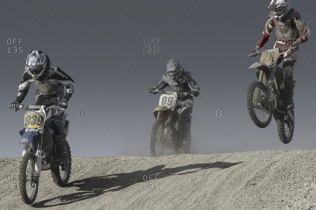 Motorcycle racers kicking up clouds of dust during race