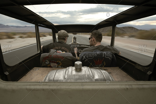 Back view of two men in a rickety car