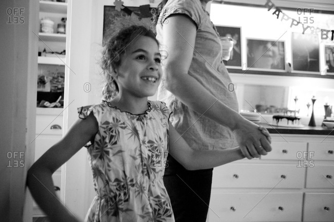 Surprised little girl standing with her mother in dining room
