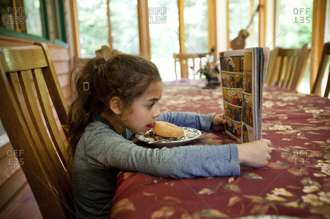 Pretty girl eating a sloppy joe and reading comic book in the dining room