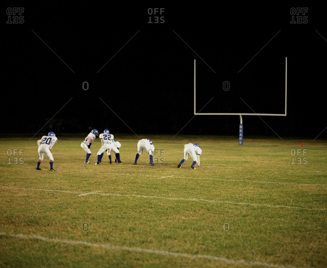 High School Football Players In Front Of A Goalpost At Night
